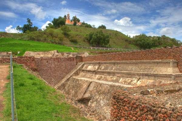 Nem a pirâmide de Gizé, nem a de Teotihuacan. A maior construção do gênero fica na Zona Arqueológica de Cholula, localizada a pouco mais de seis quilômetros da cidade de Puebla, no México. O monumento ainda não foi totalmente escavado por que os colonizadores espanhóis construíram sobre ele uma igreja católica que também é considerada um patrimônio histórico