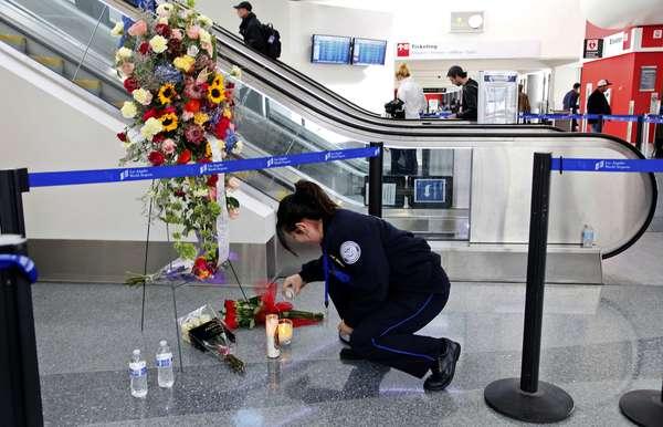 4 de novembro - A agente de segurança aeroportuária Alexa Mendoza acende vela em memorial montado em homenagem a colega morto no terminal 3 do aeroporto de Los Angeles
