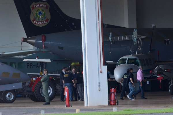 16 de novembro - Avião da PF com condenados do mensalão chega ao aeroporto de Brasília. Na foto, José Genoino (de camisa rosa) é conduzido por policiais federais