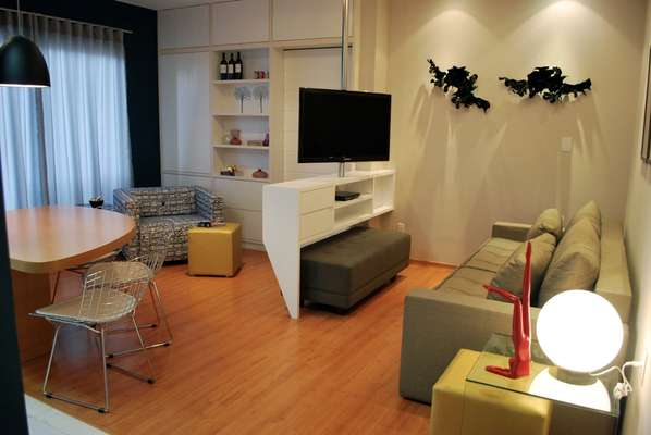 Neste projeto de 48m², a disposição da sala de TV foi alterada, com inclusão de uma marcenaria com suporte giratório para atender aos três ambientes
