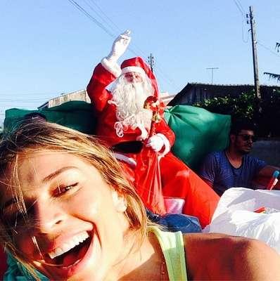 Com o paio vestido de Papael Noel, Grazi Massafera saiu pelas ruas e distribuiu presentes para crianças, na tarde desta quarta-feira (25)