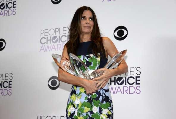 """A atriz Sandra Bullock conquistou, na noite dessa quarta-feira (8), quatro prêmios no People's Choice Awards, em Los Angeles. Indicada em 14 das 60 categorias, ela saiu com os prêmios de melhor atriz, melhor atriz de comédia (por As Bem-Armadas) e melhor atriz dramática graças a Gravidade, um filme que também lhe valeu o título de """"melhor dupla do cinema"""" junto com George Clooney"""