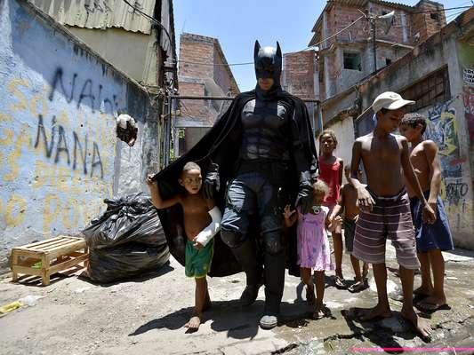 Homem fantasiado de Batman alegra as crianças no momento da retirada dos moradores da Vila do Metrô