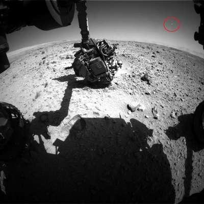 """O blog UFO Sightings Daily afirma que a sonda Curiosity registrou um óvni nos céus de Marte. Segundo o texto, o objeto parece se mover para o canto superior direito da imagem. Segundo o jornal Daily Mail, os """"óvnis"""" em Marte são descartados como sendo meteoros. Veja a seguir outras teorias da conspiração sobre o planeta vermelho."""