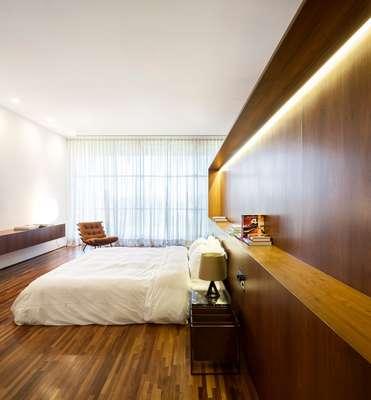 O quarto quase todo de madeira perde a rusticidade com o projeto de iluminação discreto e eficiente