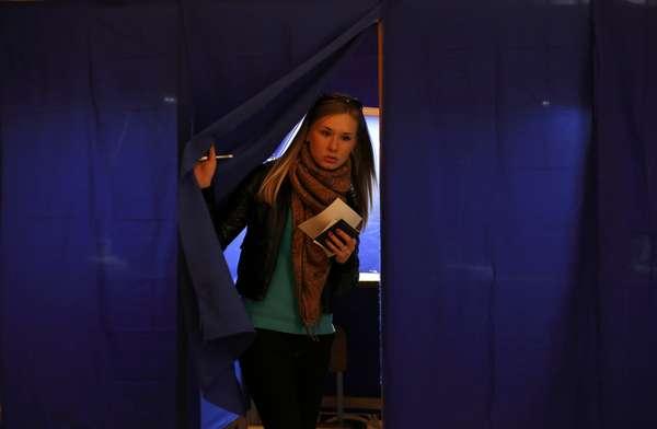 Jovem sai da cabine de votação após registrar seu voto no referendo da Criméia