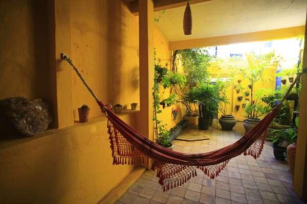 O espaço de relaxamento depende do perfil do morador e do que a casa pode comportar. Aqui, um canto zen com uma cara bem brasileira. Não poderia faltar a tradicional rede preguiçosa, como diz a canção A Majestade, O Sabiá, de Roberta Miranda