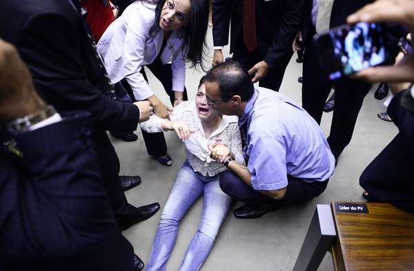 Sessão solene no plenário da Câmara rememora os fatos relacionados ao dia 31 de março de 1964, véspera do golpe de Estado que deu origem à ditadura militar. Na foto, mulher passa mal ao visualizar homenagem a militares levada pelo deputado Jair Bolsonaro