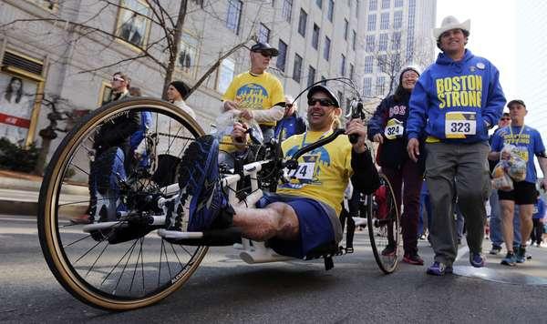 Marc Fucarile, sobrevivente que perdeu uma perna no atentado da Maratona de Boston em 2013, conduz seu triciclo de mão durante a Corrida em Tributo à maratona, neste sábado (19)