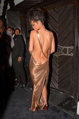 """Depois de aparecer com o vestido transparente na semana passada, Rihanna usou nesta segunda-feira (05), no evento """"afterparty"""", após o baile do Metropolitan Museum, um vestido dourado com decote atrás que dá para ver mais do que deveria: o começo do bumbum. Corajosa a moça, né?"""