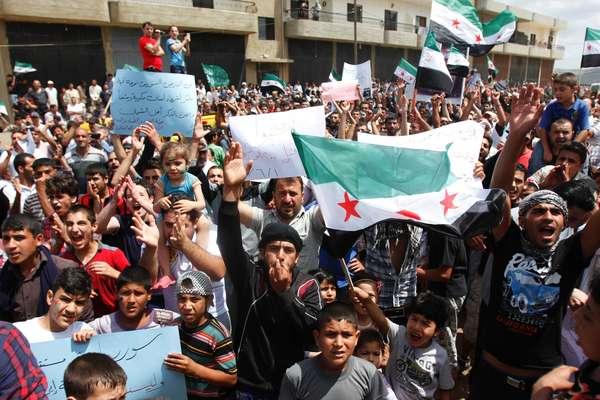 Refugiados sírios exibem bandeiras do Exército Livre da Síria durante manifestação contra o pleito desta terça-feira, 3 de junho, em Trípoli, Líbano