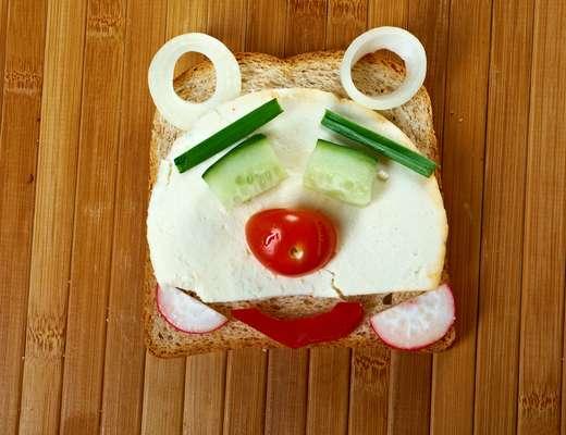 """Faça o sanduíche de """"urso"""": em uma fatia de pão de forma integral coloque queijo branco, tomate cereja, pepino, cebolinha, pimentão vermelho, rodelas de cebola e rabanete"""
