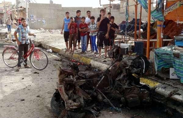 06 de junho - Jovens iraquianos observam os danos causados após a explosão de um carro-bomba na cidade de Kirkuk