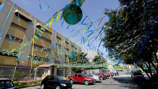 Um conjunto residencial em Brasília está coberto de verde e amarelo: bandeirinhas e pinturas são vistas por toda parte. A sede do Estádio Mané Garrincha, que recebeu Colômbia x Costa do Marfim na última quinta-feira, agora se prepara para o jogo do Brasil na próxima segunda-feira, contra Camarões, às 17h