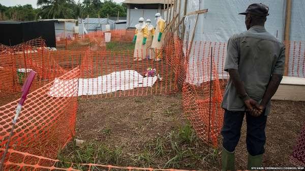 """A Organização Mundial da Saúde (OMS) disse que """"medidas drásticas"""" devem ser tomadas para conter o surto de ebola na África Ocidental, que já matou cerca de 400 pessoas. É o maior surto em números de casos, número de mortes e em distribuição geográfica. Na foto, uma equipe está próxima ao corpo de uma vítima"""