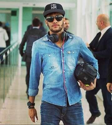 """""""Para o look totalmente índigo, o Neymar está correto, seja na diferente mistura das lavagens da camisa e da calça jeans. Os acessórios (óculos, relógio, pulseira e boné) estão ok, mas o erro é carregar um nécessaire no lugar de uma bolsa"""", analisa Mario Queiroz"""