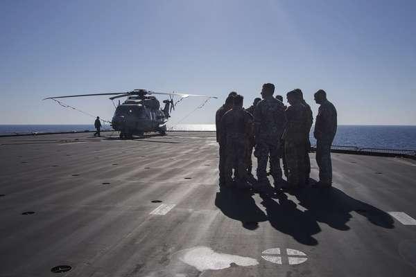 Tripulação um helicóptero se prepara para patrulhar o mar em busca de barcos carregando imigrantes. Em um espaço de seis horas, quatro barcos foram resgatados