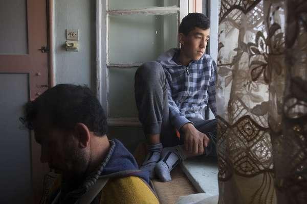 Malak, 13, olha pela janela do apartamento onde mora com seu pai e outros dois refugiados em Atenas