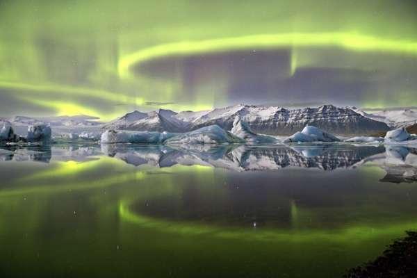 A aurora verde e vívida que cruza o céu noturno islandês é refletida na lagoa glacial de Vatnajökull, no Parque Nacional Jökulsarlon. A imagem foi tirada pelo fotógrafo britânico James Woodend, que ganhou o prêmio de Fotógrafo da Astronomia de 2014.