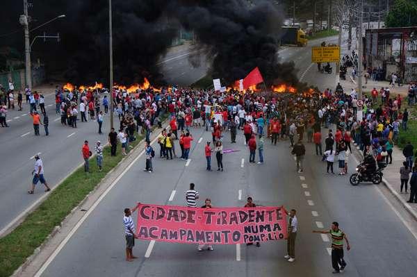 Na avenida Jacu-Pêssego, na zona leste, cerca de 100 pessoas participam da manifestação e atearam fogo em pneus