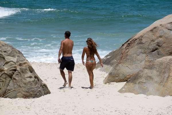 Casal caminha na areia da praia do Abricó, no Recreio dos Bandeirantes, Rio de Janeiro