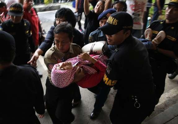 Seguranças do aeroporto de Surubaia (Indonésia) carregam parente desmaiada de um dos passageiros que estava a bordo do avião da AirAsia