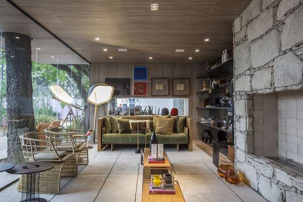 A dupla Gil Cioni e Olegário Sá criou a Casa da Árvore, que funciona como uma cabana de praia ou montanha construída 100% de materiais sustentáveis. O ambiente usa obras de arte brasileiras e aproveita as árvores do próprio Jockey Club com parede de vidro.