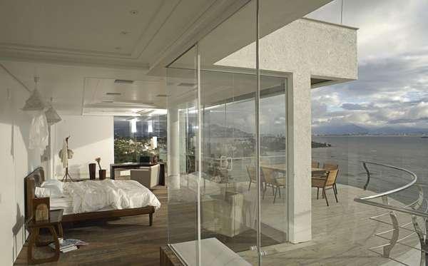 Todo envidraçado, este quarto de casal projetado por Mantovani e Rita privilegia a vista para o mar e o design clean