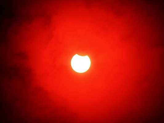 Primeiro eclipse solar do ano em São Paulo, foto feita com filtro de proteção vermelha.