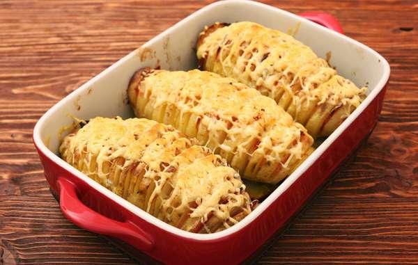 A receita é simples e deliciosa! Ingredientes: batatas, manteiga para pincelar por cima e recheio. Modo de preparo: laminar as batatas com a faca de modo que não chegue até o final, caso contrário, vai virar chips. Depois coloque o recheio dentro, pode colocar mais coisas além do queijo, por exemplo, bacon e temperos, ok? Dê o último toque pincelando toda a superfície com manteiga derretida. Para finalizar, só enfileirar as batatas em uma assadeira e levar para o forno em fogo alto por uma hora.