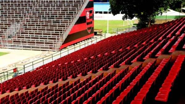 Cadeiras em vermelho na tribuna e setor Sul (espaço dos visitantes), ao fundo, com símbolo do Flamengo