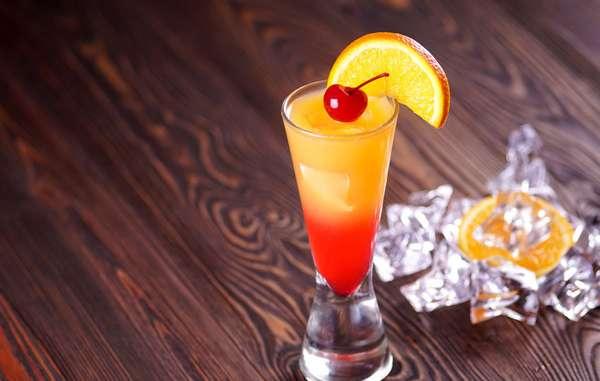 """Tequila SunriseA bebida é uma das mais famosas, junto com o """"Sex On The Beach"""". Ingredientes: 1 dose de tequila dourada 3 doses de suco de laranja (gelado) 1 dash de Grenadine (substituível por Groselha) 1 colher de açúcar (ou não, depende do suco de laranja) Modo de preparo: Coloque a tequila, o suco e o açúcar em um copo e misture. Depois coloque a Grenadine ou groselha. Gelo a gosto. Receita do Papo de Bar"""