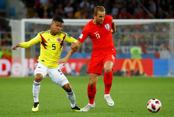 Harry Kane, o artilheiro da Copa, domina a bola observado por Barrios