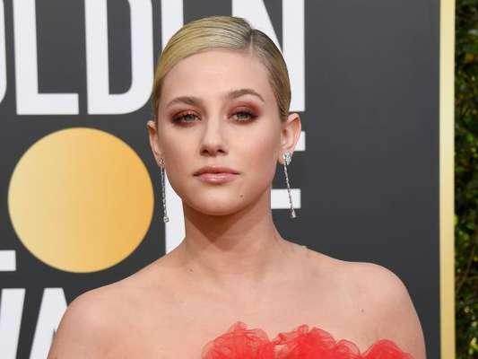 Atriz da série 'Riverdale', Lili Reinhart apostou na sombra laranja para combinar com o vestido coral no Globo de Ouro 2019