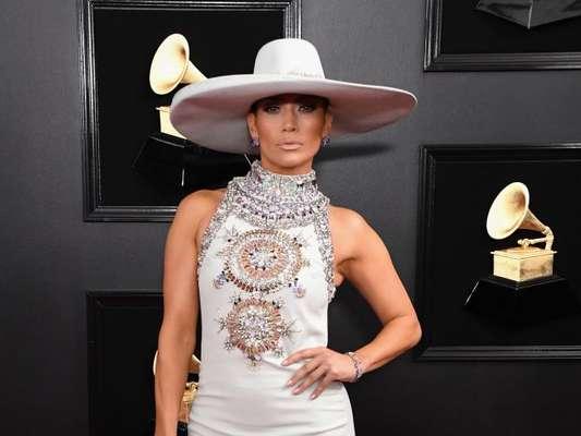 Chapéu no tapete vermelho? Temos! Jennifer Lopez foi quem apostou no acessório para combinar com o vestido longo off white no Grammy Awards 2019