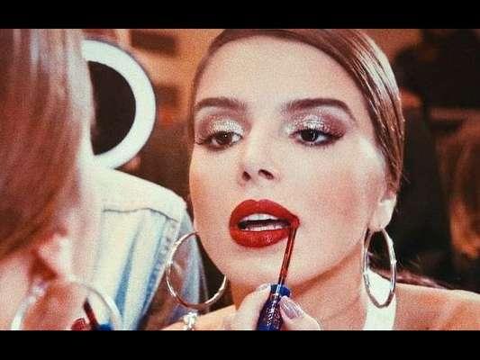 Giovanna Lancellotti passa o batom vermelho com muito cuidado nos lábios. Cor deixou o visual da atriz mais sofisticado