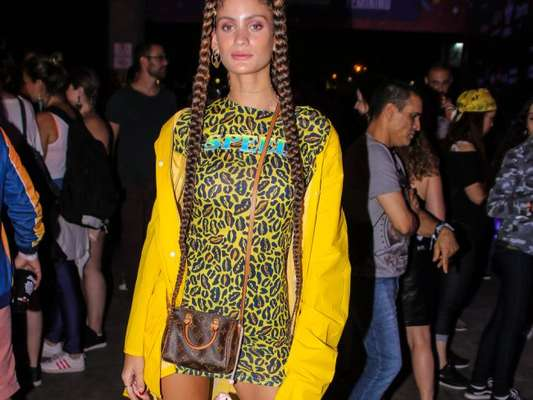 Looks dos famosos do Lollapalooza: Laura Fernandez usou mix de animal print com fundo amarelo, casaco amarelo vibrante oversized e dad sneaker branco. As boxer braids deixaram o visual com mais estilo ainda