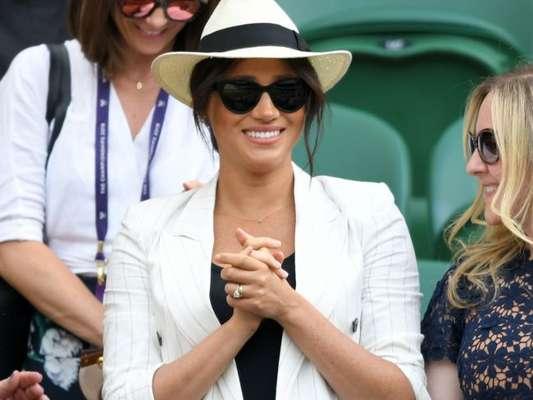 Meghan Markle assistiu a amiga Serena Williams em Wimbledon (em julho de 2019): o look incuía jeans, t-shirt preta e chapéu panamá, mas o que chamou a atenção foi o cordão em ouro com a letra 'A', de Archie