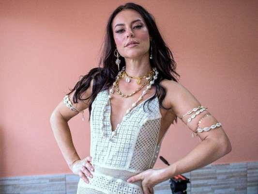 Paolla Oliveira usou vestido branco e acessórios com búzios para gravar o clipe da Grande Rio