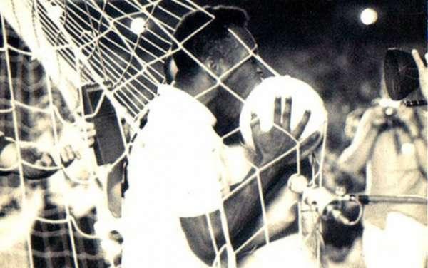 Após balançar o 'véu da noiva' do Maracanã, Pelé beija a bola com a qual marcou seu gol de número mil na carreira